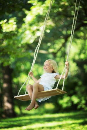 swinging: Little smiling girl on a swing
