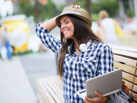 Smiling girl with laptop outdoors photo