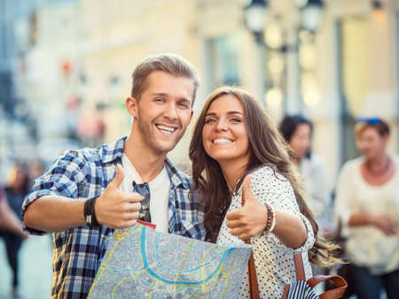 Looking couple with a map outdoors Reklamní fotografie - 37572893