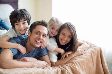 Familie mit Kindern auf dem Bett