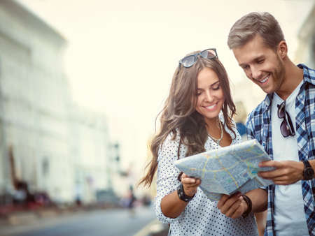 vacation: Smiling couple with a map outdoors Stock Photo