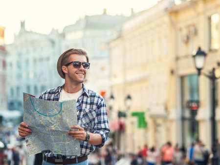city people: Young man with a map outdoors