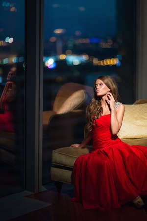 girl in red dress: Beautiful young girl in a red dress in the apartment