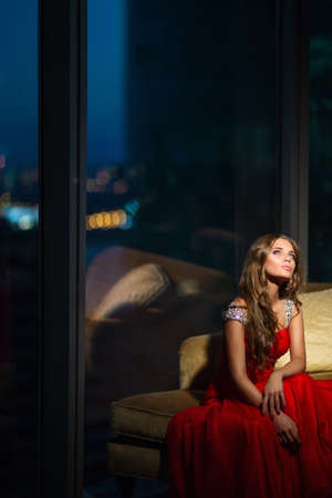 girl in red dress: Beautiful girl in red dress indoors Stock Photo