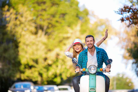 road of love: Smiling people on a scooter Stock Photo