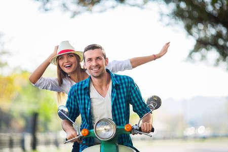 person traveling: Pareja feliz en una moto al aire libre