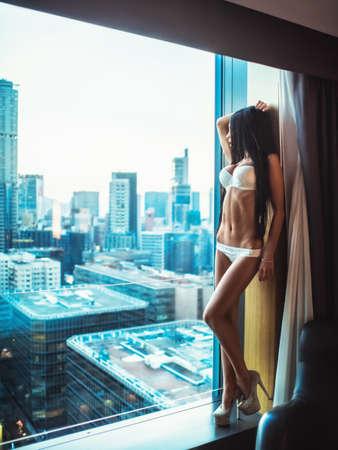 Muchacha hermosa en ropa interior en la ventana