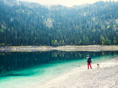 travel locations: Young man with dog walks near the lake
