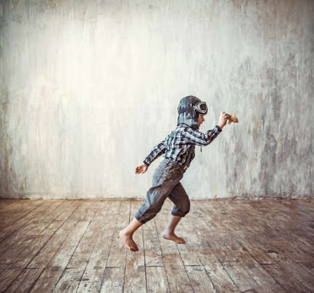 Running boy with plane indoors