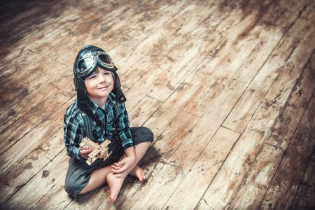 pilot helmet: Little boy with the airplane on the floor Stock Photo
