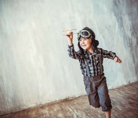 pilotos aviadores: Niño feliz que se ejecuta con el plano Foto de archivo