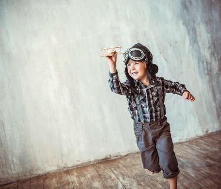 dzieci: Szczęśliwy chłopiec biegający z samolotu