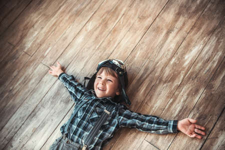 wood floor: Laughing boy on the floor Stock Photo
