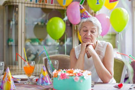 urodziny: Sad starsza kobieta na przyjęciu urodzinowym Zdjęcie Seryjne