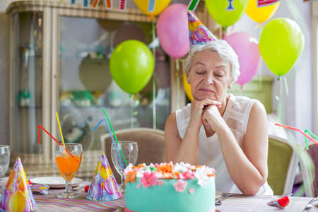 compleanno: Triste donna anziana ad una festa di compleanno Archivio Fotografico