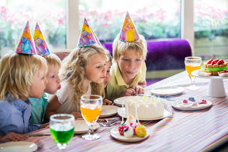 blow out: Children blow out the candles on the cake