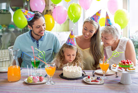 children birthday: Little girl blows out the candles on the cake Stock Photo