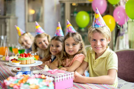 birthday presents: Children at a birthday party at home Stock Photo