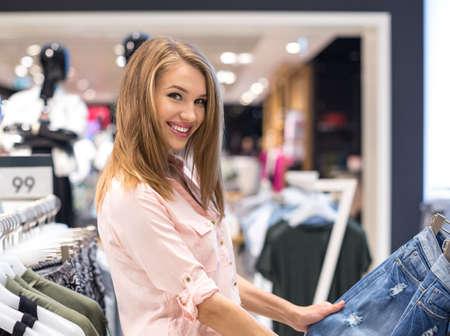 tienda de ropa: niña sonriente en la tienda