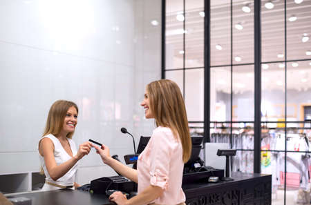 credit cards: Young women with credit card in the store