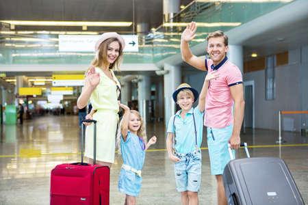 mujer con maleta: Familia feliz con una maleta en el aeropuerto Foto de archivo