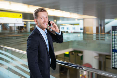 通信: Businessman speaking on the phone at the airport