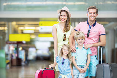 family vacation: Happy family with a suitcase at the airport
