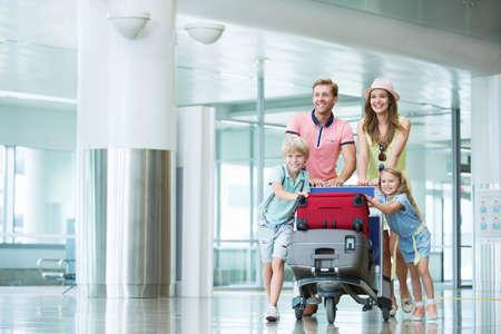 viaje familia: Familia sonriente con los niños en el aeropuerto