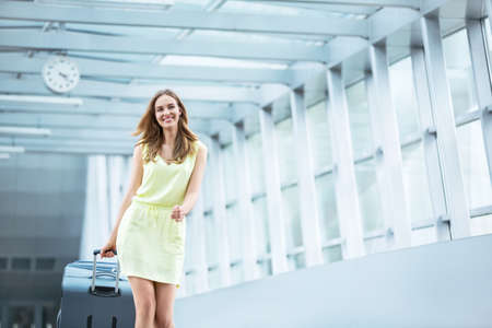 mujer con maleta: Muchacha sonriente con una maleta en el aeropuerto Foto de archivo
