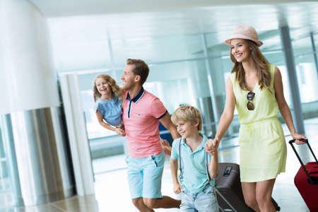 Lächelnde Familie mit Kindern auf dem Flughafen