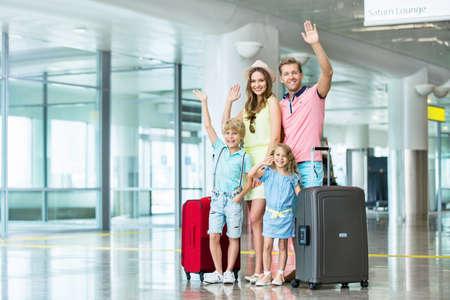 Glückliche Familie mit einem Koffer auf dem Flughafen Standard-Bild - 45036268