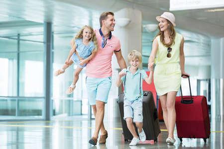 Lachende familie met kinderen op de luchthaven Stockfoto