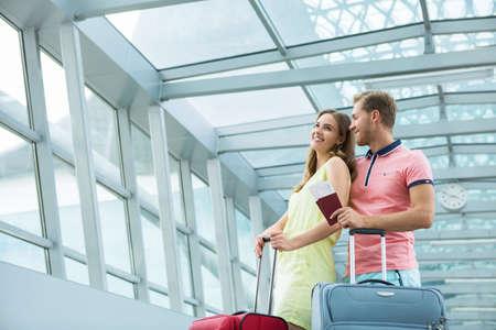 valise voyage: Jeune couple avec une valise à l'aéroport