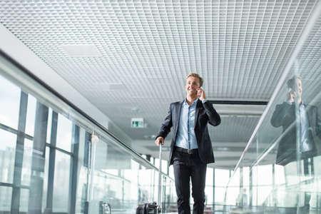 通信: 空港で携帯電話で話すビジネスマン