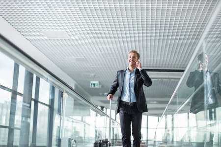 gente aeropuerto: Hombre de negocios hablando por teléfono en el aeropuerto