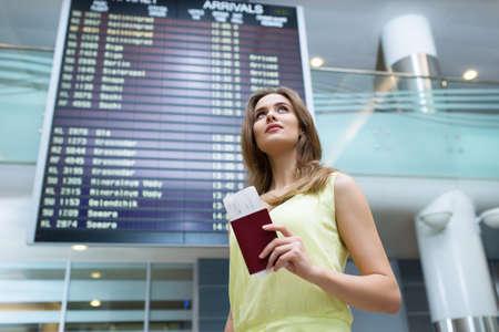 Jonge vrouw met een paspoort op het bord