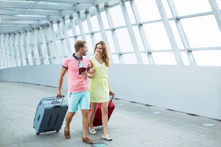 Glimlachend paar met een koffer op de luchthaven Stockfoto
