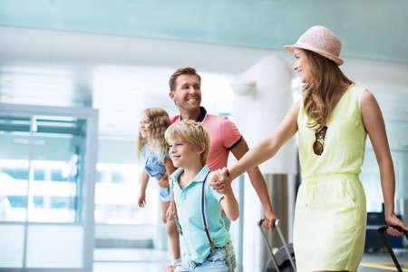 Familia feliz con los niños en el aeropuerto