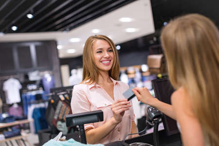 retail: Woman at the checkout makes shopping Stock Photo