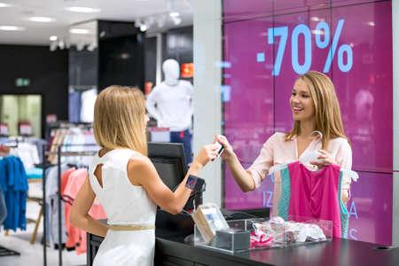 Junges Mädchen an der Kasse macht das Einkaufen Standard-Bild
