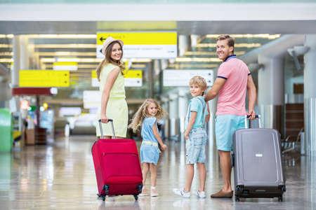 空港でスーツケースを持つ家族