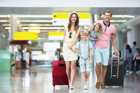Happy family with suitcases in the airport. Stock Photo
