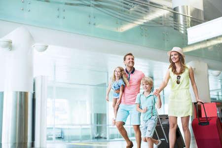 mujer con maleta: Familia feliz en el aeropuerto