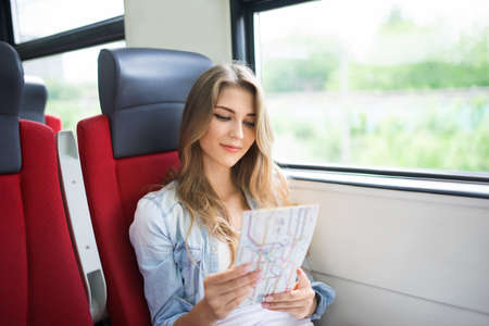 railway transportations: Young woman with a map in the train Stock Photo