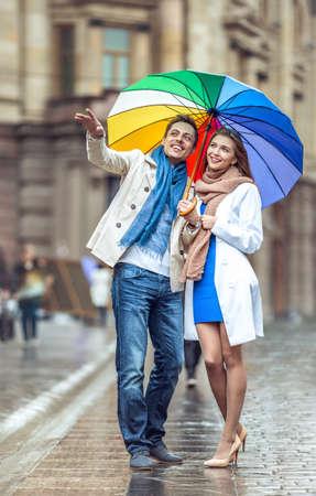 UOMO pioggia: Giovane coppia con un ombrello per la strada