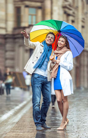 love in rain: Young couple with an umbrella on the street