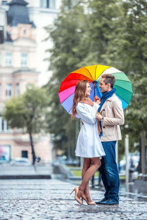 woman with umbrella: Young couple with an umbrella
