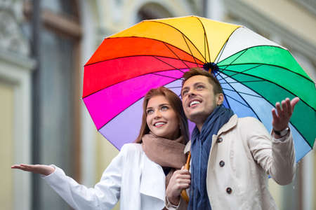 UOMO pioggia: Coppie felici con un ombrello per la strada