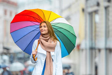 autumn colour: Young girl with an umbrella on the street Stock Photo