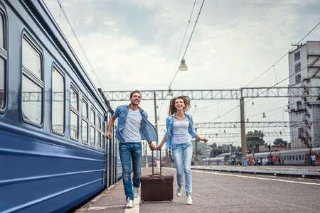 鉄道駅にスーツケースを持ってのカップルを実行しています。